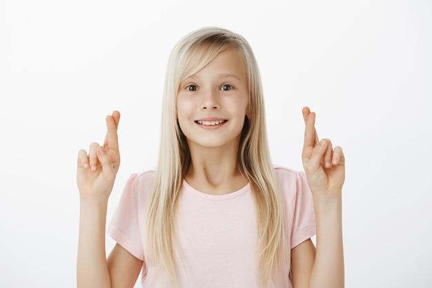Mädchen hofft, dass der weihnachtsmann ihr haus mit einem riesigen geschenk besuchen wird. grinsende verträumte junge tochter mit blonden haaren, hände heben mit gekreuzten fingern und lächeln vor staunen und verlangen, hoffen oder wünschen
