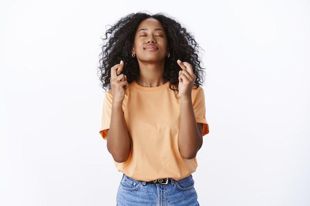 Mädchen hofft, dass gott gebete hört, die den wunsch erfüllen. hoffnungsvolle attraktive junge studentin wünscht, dass sie die universitätsprüfungen besteht, schließen sie die augen, heben sie den kopfhimmel, kreuzen sie die finger, viel glück, weiße wand