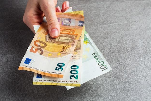 Mädchen holt eine banknote von fünfzig euro aus der braunen lederbrieftasche heraus. hände, geld und brieftasche nahaufnahme. nächstenliebe. grauer hintergrund. foto von geld. zahlung. horizontales foto.
