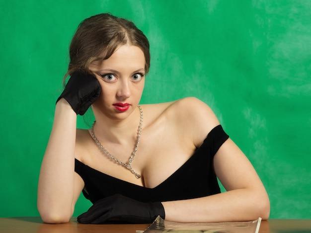 Mädchen im abendkleid, das am tisch sitzt. studioportrait im retro-stil
