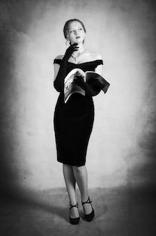 Mädchen im abendkleid, das mit zeitschrift in den händen aufwirft. schwarz-weiß-porträt im studio