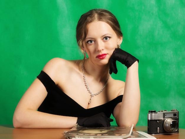 Mädchen im abendkleid, das mit zeitschriften am tisch sitzt. studioportrait im retro-stil