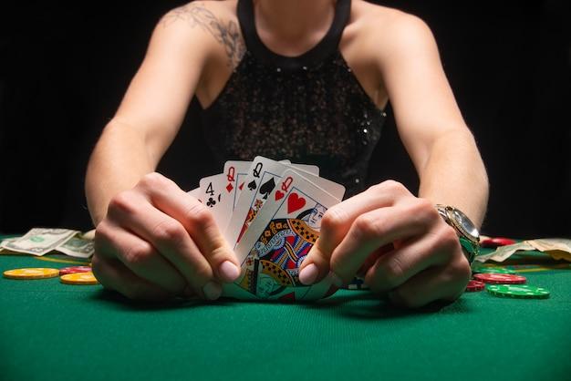 Mädchen im abendkleid, das poker spielt und karten betrachtet