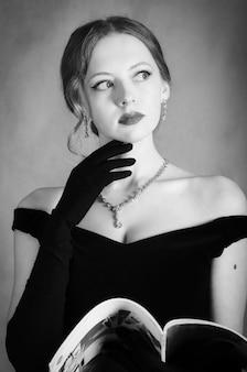 Mädchen im abendkleid mit zeitschrift in den händen. schwarz-weiß-porträt im studio
