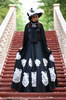 Mädchen im alten retro-kleid auf der treppe im freien