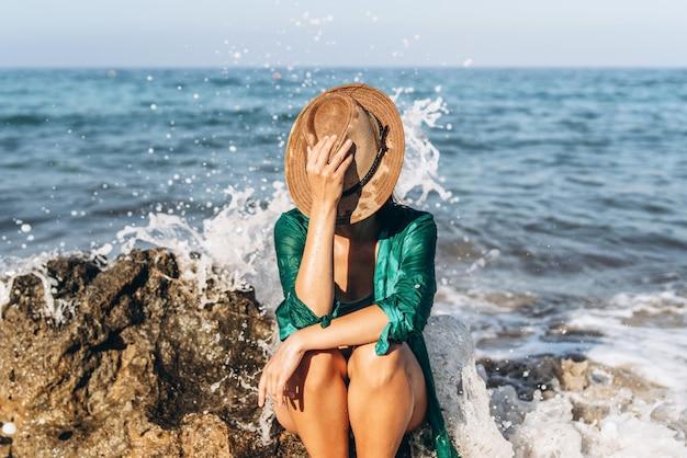 Mädchen im badeanzug, der auf dem strand nahe dem meer in grünem pareo sich entspannt.