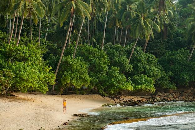 Mädchen im badeanzug geht auf einem tropischen strand