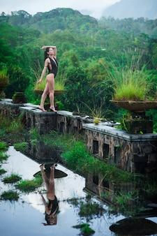 Mädchen im badeanzug im mystischen verlassenen faulen hotel in bali mit blauem himmel.