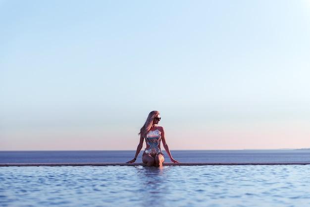 Mädchen im badeanzug im pool, blick von hinten