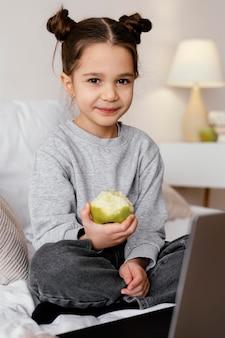 Mädchen im bett, das video auf laptop sieht