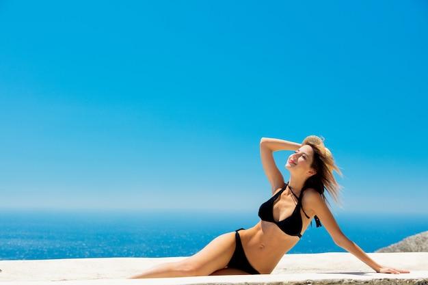 Mädchen im bikini mit blauem meer und himmel auf hintergrund