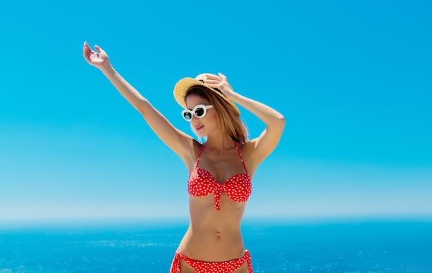 Mädchen im bikini mit blauem meer und himmel im hintergrund