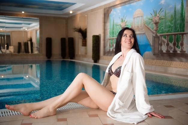 Mädchen im bikini nahe dem pool. schönheitsbehandlung. wellness. konzept für einen gesunden lebensstil.