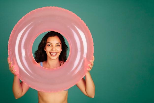 Mädchen im bikini suchen durch aufblasbaren ring