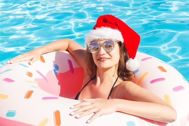 Mädchen im bikini und im weihnachtsmannhut mit aufblasbarem rosa kreis des donuts