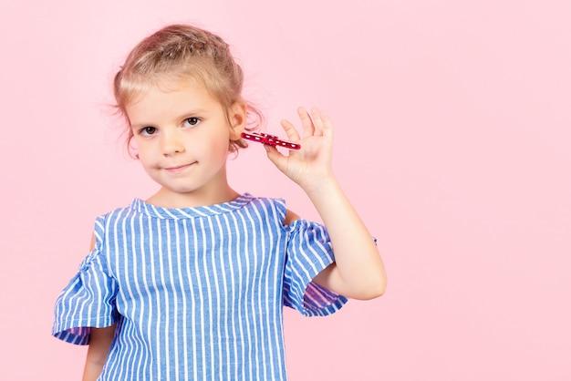 Mädchen im blauen abgestreiften hemd spielt roten spinner in der hand