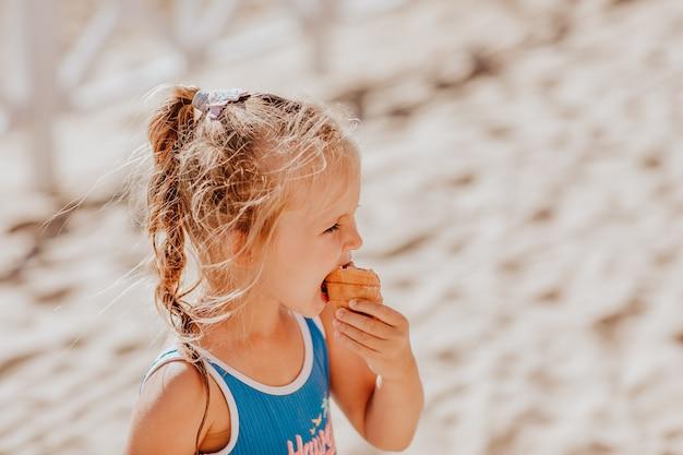 Mädchen im blauen badeanzug, der eiscreme am strand isst.
