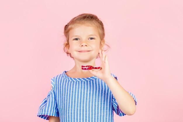 Mädchen im blauen gestrippten hemd spielt roten spinner in der hand