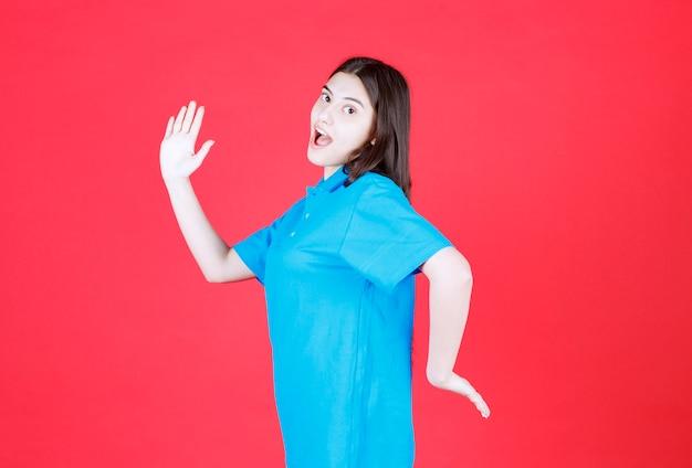 Mädchen im blauen hemd, das auf roter wand steht und wegläuft.