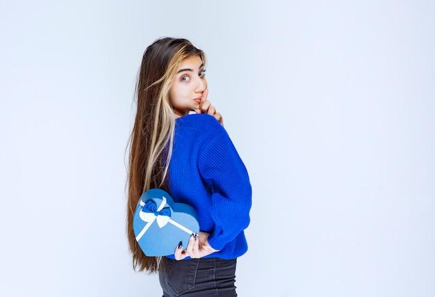 Mädchen im blauen hemd, das eine blaue herzform-geschenkbox hinter sich versteckt.