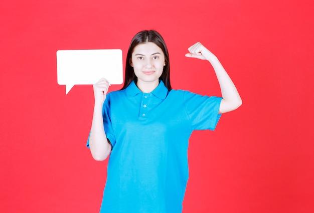 Mädchen im blauen hemd, das eine rechteckige infotafel hält und positives handzeichen zeigt