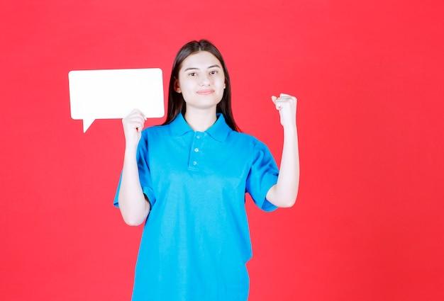 Mädchen im blauen hemd, das eine rechteckinfotafel hält und positives handzeichen zeigt.