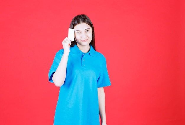 Mädchen im blauen hemd, das ihre visitenkarte darstellt und nachdenklich schaut.