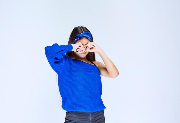 Mädchen im blauen hemd, das sich schläfrig fühlt.
