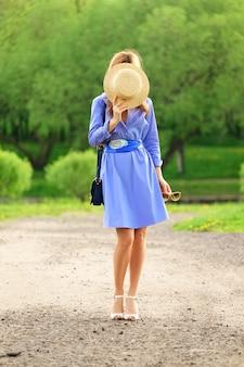 Mädchen im blauen kleid bedeckt ihr gesicht mit einem hut