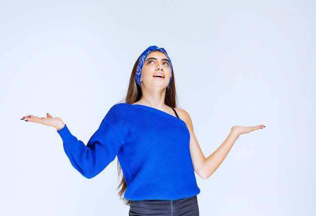 Mädchen im blauen partyhemd, das auf etwas herum zeigt.