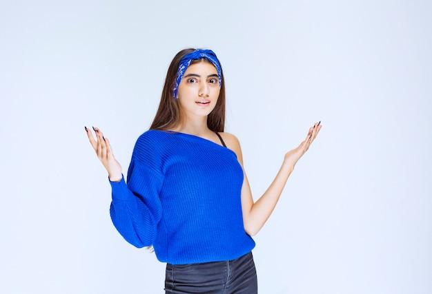 Mädchen im blauen partyhemd, das oben etwas darstellt.