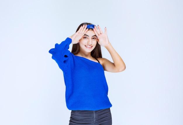 Mädchen im blauen partykleid, das den kopf hält, während sie verwirrt und überrascht ist.