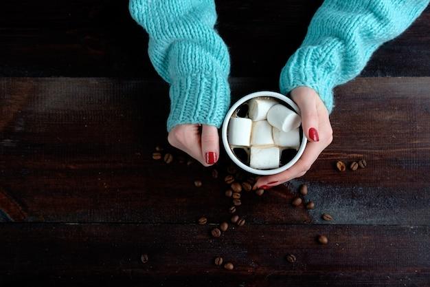 Mädchen im blauen pullover, der tasse kaffee mit marshmallowshänden hält, schließen kopienraum