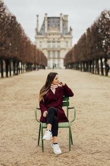 Mädchen im bordo-mantel, der auf dem stuhl vor louvre-museum in paris, frankreich sitzt.
