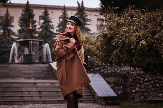Mädchen im braunen mantel fallen lächelnd in die stadt