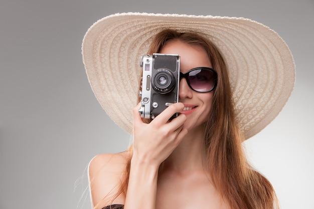 Mädchen im breitkrempigen hut und in der sonnenbrille mit retro- kamera