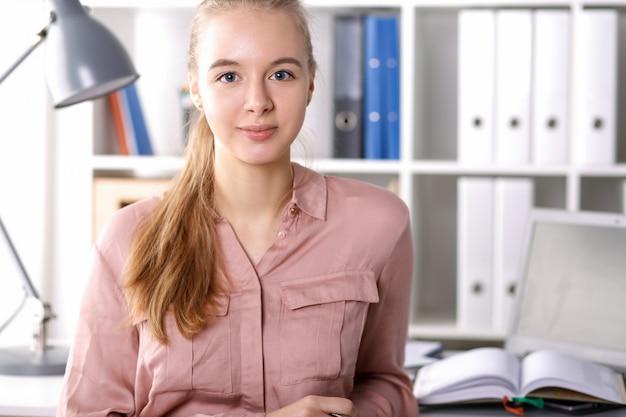 Mädchen im büro auf hintergrundordnern und büchern