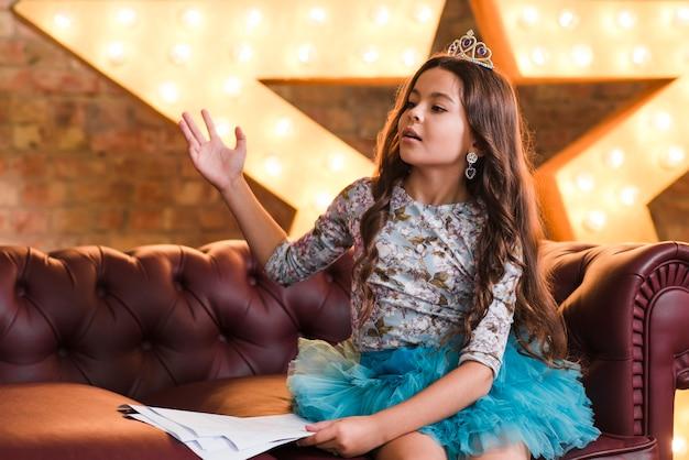 Mädchen im eleganten kleid, das auf dem sofa hält skripte sitzt