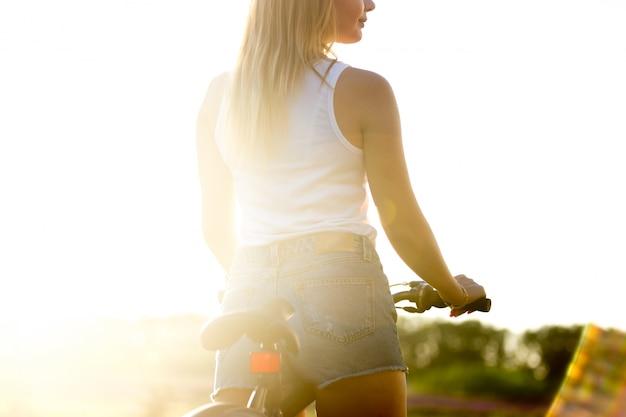 Mädchen im fahrrad bei sonnenuntergang
