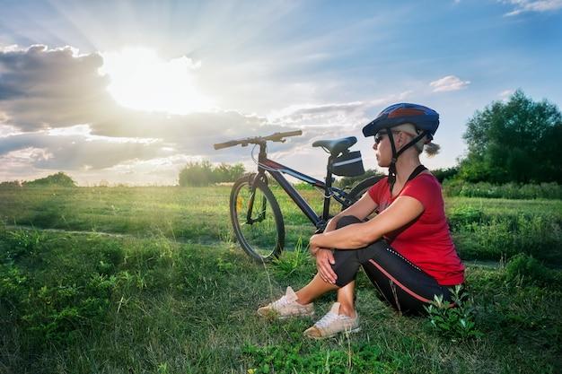 Mädchen im fahrradhelm sitzt nahe fahrrad und schaut auf den sonnenuntergang