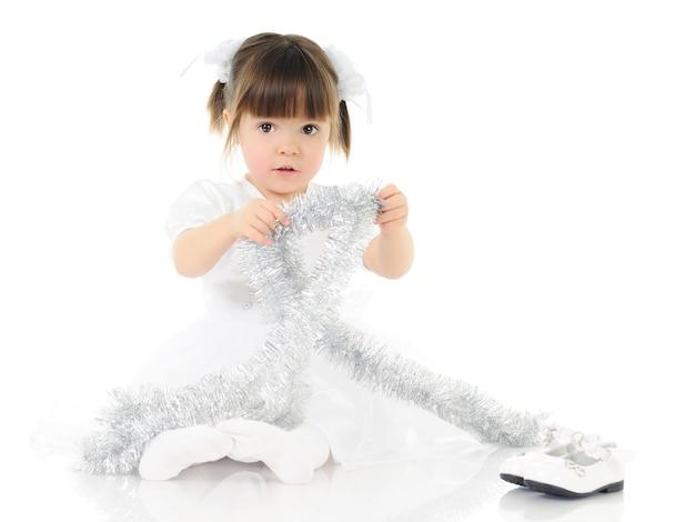 Mädchen im festlichen weißen kleid spielt mit weihnachtsdekorationen, die auf dem boden sitzen. auf weißem hintergrund isoliert