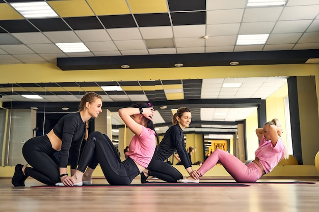 Mädchen im fitnessstudio, das übungen für die presseteamarbeit macht