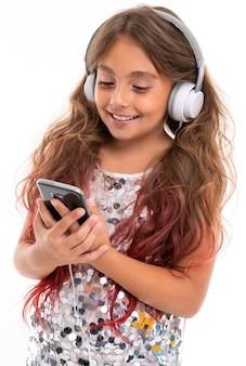 Mädchen im funkelnden kleid, mit großen weißen kopfhörern, die musik hören und auf bildschirm des schwarzen smartphones isoliert starren