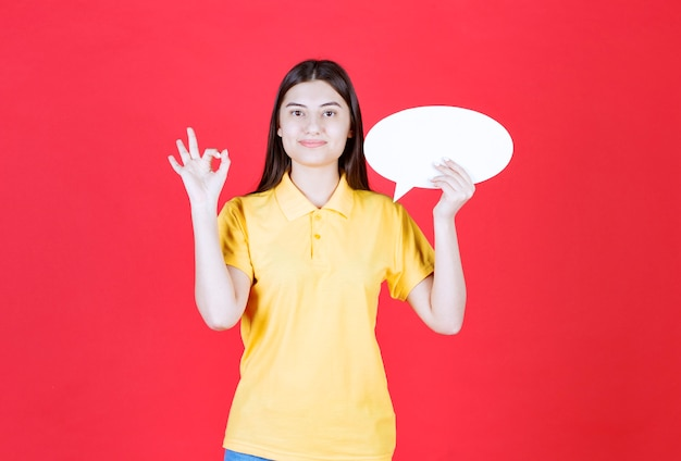Mädchen im gelben dresscode, das eine ovale infotafel hält und ein positives handzeichen zeigt