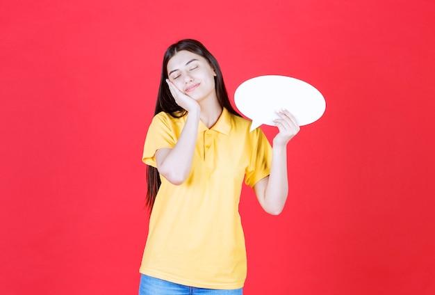 Mädchen im gelben dresscode, das eine ovale infotafel hält und schläfrig und müde aussieht