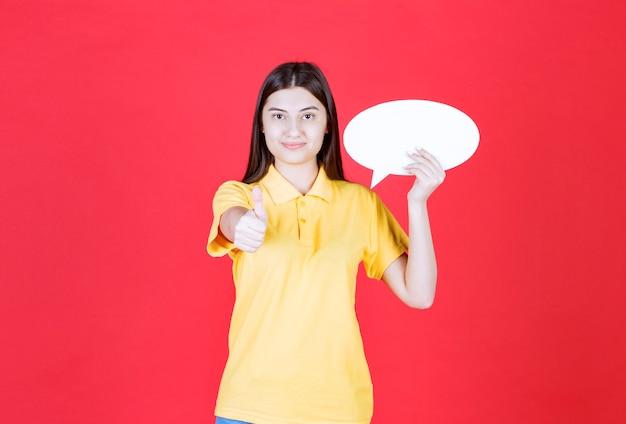 Mädchen im gelben dresscode, der eine ovale infotafel hält und positives handzeichen zeigt.