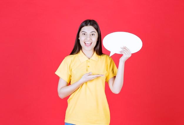 Mädchen im gelben dresscode, der eine ovale infotafel hält.