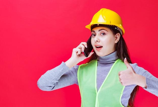 Mädchen im gelben helm, der mit dem telefon spricht und daumen zeigt.