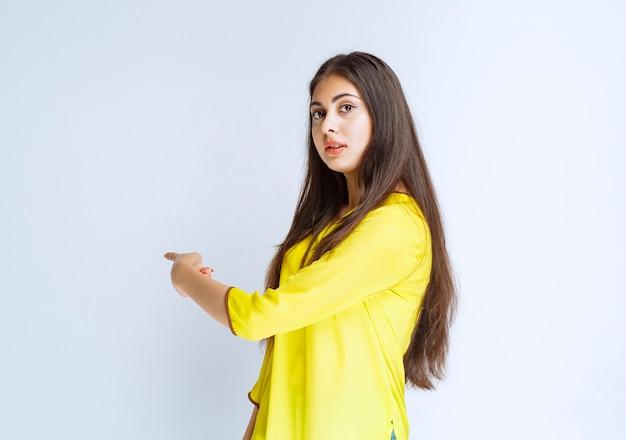 Mädchen im gelben hemd, das auf irgendwo zeigt.