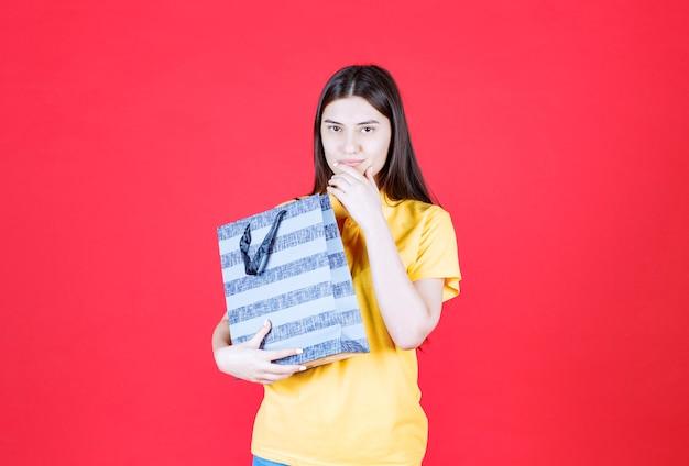 Mädchen im gelben hemd, das eine blaue einkaufstasche hält und eine gute idee denkt oder hat.